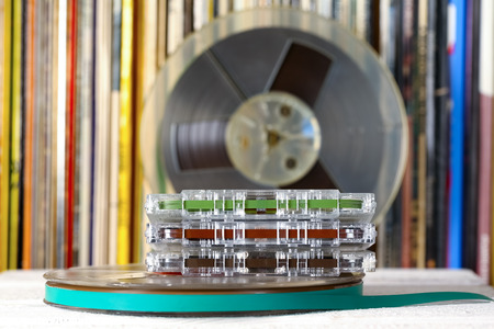 Compact cassettes and reel tapes are shown on the background of vinyl records Stock Photo