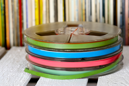 Retro music tapes are shown on a background created by vinyl records collection Stock Photo