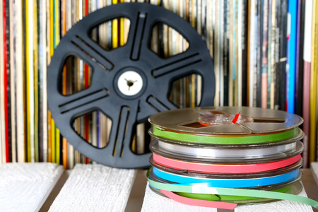 Several sound recording tapes are shown on the background of vinyl records