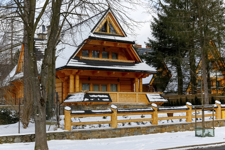 Zakopane, Poland - March 21, 2018: During winter season, a log house with a steep roof can be seen in the area fenced with a wooden fence. Banque d'images - 117150427