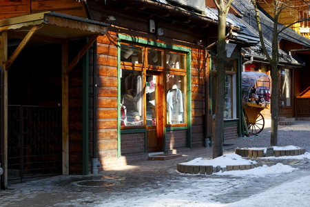 Zakopane, Poland - March 22, 2018: Shop window with clothes on sale visible inside. It is in a wooden building, which is located by the Krupowki street, which is the main shopping street in the city. Editorial