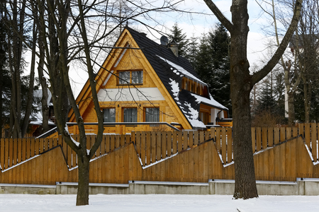 Zakopane, Poland - March 21, 2018: The wooden building hidden behind the wooden fence is covered with a steep roof. Around there are some trees without leaves because it is wintertime. Banque d'images - 117150568