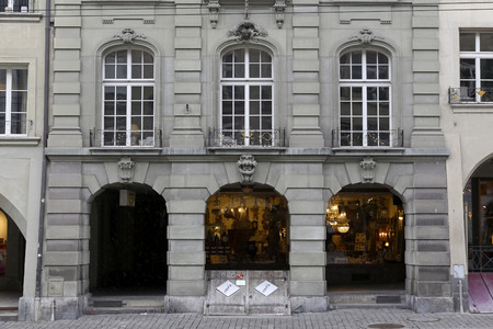 Bern Switzerland - February 21, 2018: A historic tenement house with beautiful arcades and large windows and wooden sloping doors to the basement seen just at the pavement.