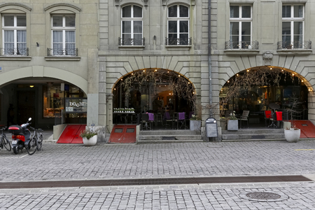 Bern Switzerland - February 21, 2018: At the cobbled street there is a historic tenement house with arcades. The famous Bernese cellars with its wooden, sloped front door, painted red are seen.