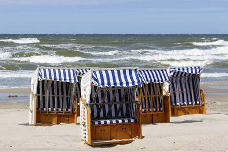 There are beach chairs with small roofs which protects against the sun are placed on a sandy beach on the Baltic coast in Kolobrzeg, Poland. Фото со стока