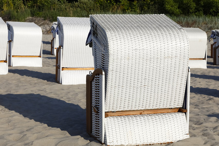 The roofed beach chairs are located on the Baltic sea beach in Poland in Kolobrzeg