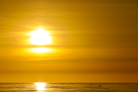 The sun is setting over the Baltic Sea in Poland. This view of sunset is seen from the beach in Kolobrzeg