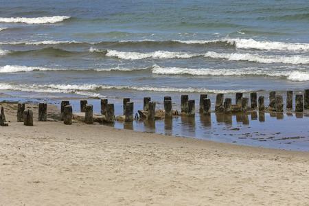Those thick wooden poles are deeply hammered into the seabed to protect seashore from the devastating effects of large sea waves. It is a sandy beach in Kolobrzeg , Poland. Stock Photo