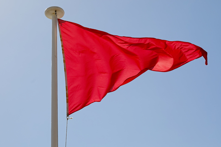The wind blows a red triangular flag, which is placed on the mast for warning purposes.