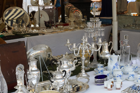 Nice, France - 17 September 2018: Candlestick and other silver items can be seen at the flea market in Cours Saleya, the famous city market offering antiques and many other products. Archivio Fotografico - 117152661