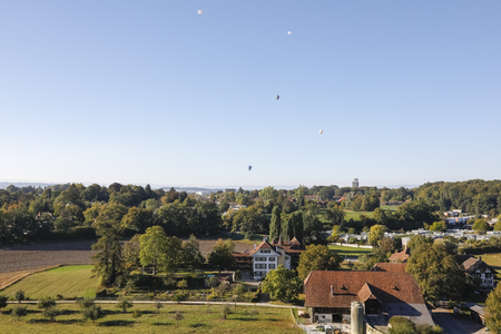 Bern Switzerland - September 27, 2018: Agricultural buildings, beautiful Wittigkofen Castle surrounded by green areas, there are five hot air baloons in the sky. This is seen the outskirts of Bern