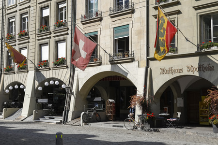 Bern Switzerland - September 14, 2018: Flags above arcades of historic tenement houses are seen along the main street and pedestrian zone in this capital city.