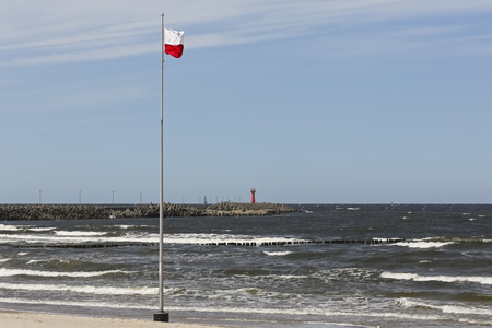 The flag of Poland is placed on a mast located on the beach, on the Baltic Sea coast in Kolobrzeg , Poland.