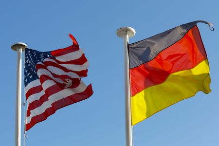 Two National Flags of both United States of America and Germany waves against clear blue sky background 版權商用圖片 - 114813591