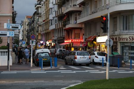 Nizza, Frankreich - 23. September 2018: Es wird dunkel, die Nacht kommt und entlang einer der Straßen werden beleuchtete Schilder von Geschäften und Restaurants eingeschaltet. Es gibt wenig Verkehr.
