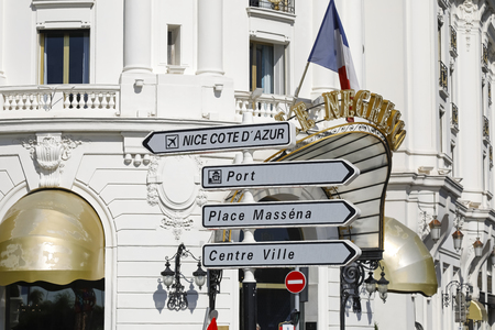 Nice, France - September 25, 2018: Road signs indicates various landmarks in the city. These orientation signs are seen against the background of the magnificent facade of the Negresco Hotel.