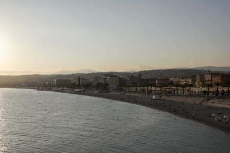 Nice, France - September 17, 2018: Cote dazur and evening view of The Bay of Angels. There are people on the beach and the buildings of the city gently illuminate the rays of the setting sun.