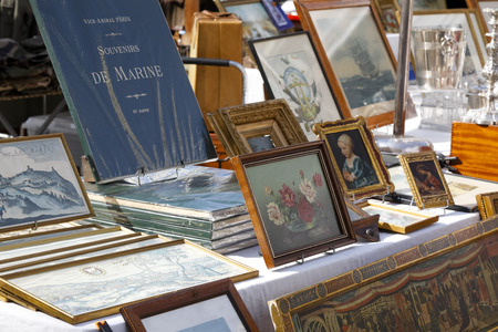 Nice, France - September 24, 2018: Paintings, books and other retro items are on sale at one of the stands at the famous Cours Saleya market.