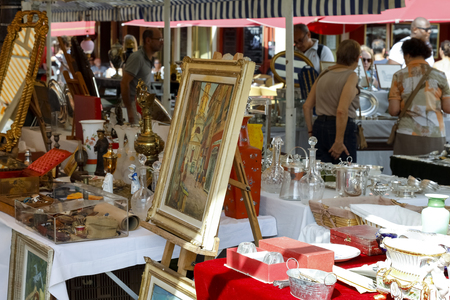 Nice, France - September 24, 2018: The framed painting and a number of other diverse items are available for sale in the flea market known as Cours Saleya. Redactioneel
