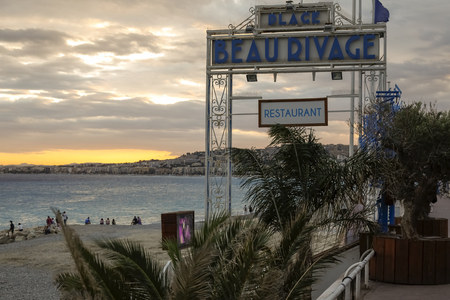 Nice, France - September 24, 2018: Despite the coming night, there are still people on the beach. The sun sets over the city.