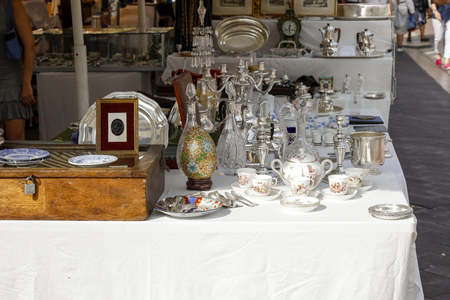 Nice, France - September 17, 2018: Retro items arranged on the stall during the famous market called Cours Saleya. There are glassware, metal, wooden products for various purposes.