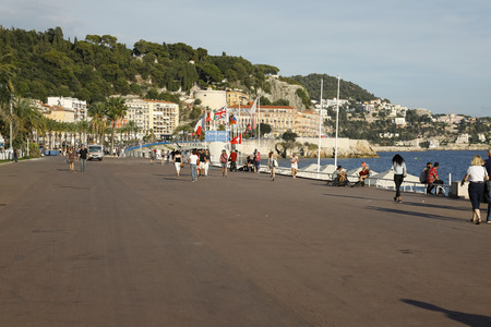 Nice, France - September 17, 2018: Wide sidewalk of the seaside promenade leading towards the Castle Hill. There are people who stroll here seeing the beautiful surrounding landscape.