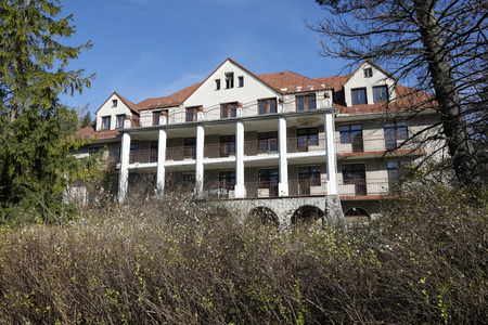 Zakopane, Poland - November 8, 2018: Among the densely growing shrubs there is a large building of the former famous and luxurious holiday house called Bristol, dating back to the early 20th century.