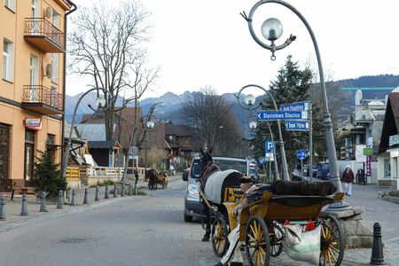 Zakopane, Poland - November 12, 2018: A coachman with a harnessed horse is waiting for tourists who will want to take a ride around the city. He is waiting in the street leading to the hills.