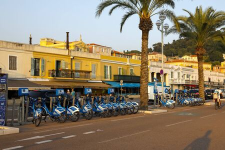 Nice, France - September 20, 2018: Bike sharing station and a little further there are small houses of former local fishermen, nowadays there are galleries in those building and restaurants and cafes.