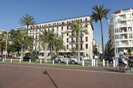 Nice, France - September 20, 2018: On the other side of the street and behind palm trees you can see a large hotel building. This is a famous hotel called Westminster.
