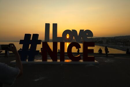 Nice, France - 20 September 2018: The following text, I Love Nice, commenced by the hashtag sign, is completed by sunset colours and a view of the Promenade des Anglais.