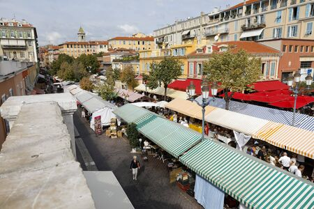 Nice, France - September 17, 2018: Rows of stalls covered with striped canvas roofs. Around this market called Cours Saleya various tenement houses are seen