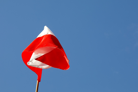 One flags of Poland which is seen in the a wind day against the background of the blue sky. This flag is seen in Zakopane , Poland