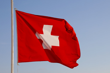 Flag of Switzerland is positioned on top of the mast and there it waves in the wind and is visible in the blue sky.