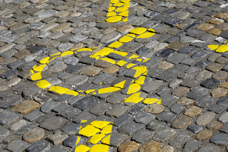 The wheelchair, which is a symbol of a disabled parking space, has been painted in yellow on a cobbled road surface . Banque d'images