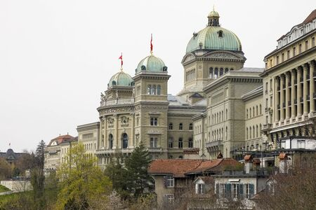 Bern, Switzerland - April 16, 2019: On a cloudy day, the large building of the Federal Palace is visible. The flags of Switzerland are on both domes.