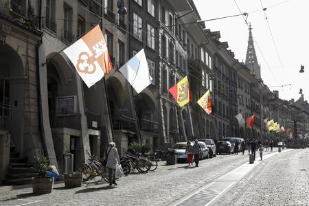 Bern, Switzerland - April 22, 2019: The facades of many historic buildings on this street are in the shade. Sun-lighted flags adorn this cobbled street, cars are parked and people walk here. Sajtókép