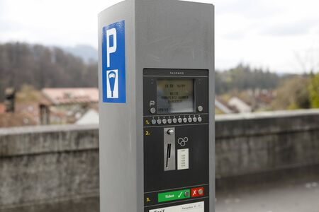 Bern, Switzerland - April 16, 2018: Self-service paid parking meter in the old town district. Paid parking helps to solve the problem of parking in the city centre.