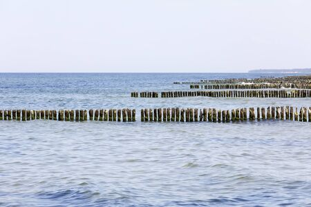 At the coast of the Baltic Sea there are rows of thick wooden poles driven into the seabed. It is the protection of the coast against the harmful effects of sea waves, here in Kolobrzeg in Poland.