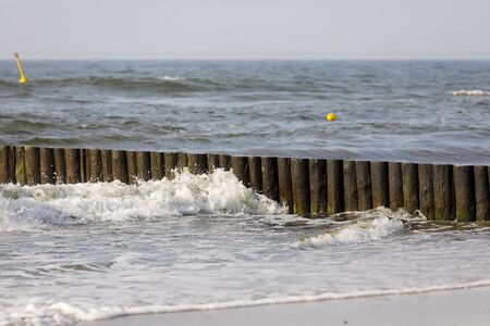 The waters of the Baltic Sea by the beach in Kolobrzeg, Poland. Thick wooden logs, being a breakwater, have been fixed to the seabed. Imagens
