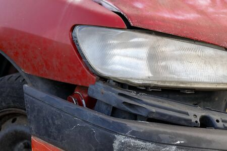 The red car has suffered an accident as a result of which it is now significantly damaged.