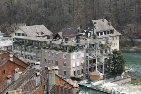 Bern, Switzerland - April 16, 2018: Town buildings on the Aare River, which flows through the town. On the other side of the river there are trees that form the background for these houses.