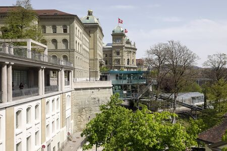 Bern, Switzerland - April 22, 2019: A large building of the Federal Palace and a small upper station of the cable car. With this cable car you can go down to Marzili. Éditoriale