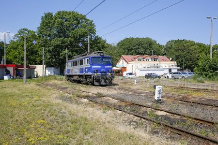 Kolobrzeg, Poland - June 18, 2019: The electric locomotive painted white and blue of PKP Intercity colors has been parked on a side-track, which is part of the railway station in the city. Editorial