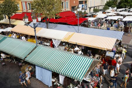 Nice, France - September 17, 2018: People walk between the stalls and watch the goods stored there. Striped canvas roofs are the hallmark of this famous market called Cours Saleya. Editorial