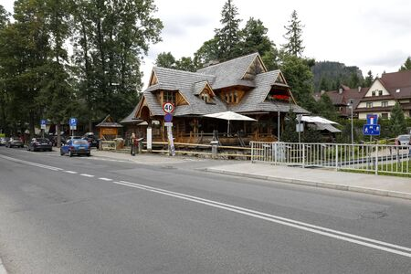Zakopane, Poland - July 09, 2019: Traditional wooden log building by the street. This building of steep roofs nowadays houses a restaurant of original name Przy Mlynie