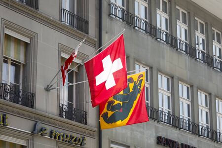 Bern, Switzerland - April 15, 2019: The flag of the canton of Valais is almost invisible, the flag of the country of Switzerland and the flag of the city of Bern, these flags have been fixed together
