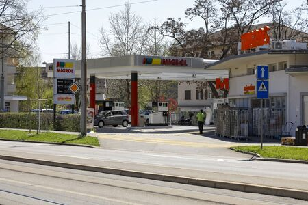 Bern, Switzerland - April 20, 2019: There is a petrol station Migrol, which is located on the other side of the street. There are trees in the immediate vicinity.