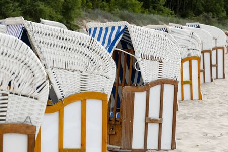 Stylish roofed chairs are in the style of an old design, which was formerly made of wicker and now you can see their modern version on the beach in Kolobrzeg in Poland 免版税图像