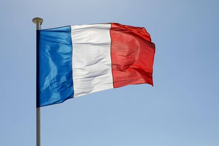 The three-colored national Flag of France waves in the wind and is visible in the blue sky.